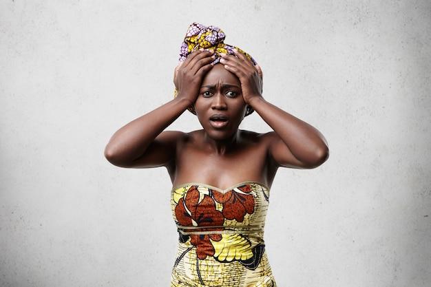 Mulher africana de meia-idade, de pele escura, com roupas tradicionais, com as mãos na cabeça e olhando em desespero por causa de alguns problemas.