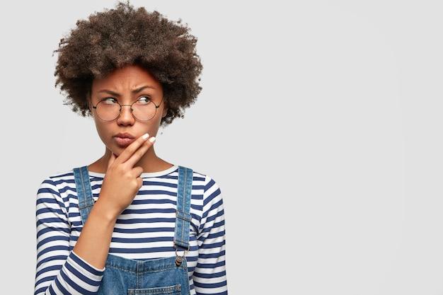 Mulher africana de pele escura pensativa segurando o queixo e olhando pensativamente para o lado