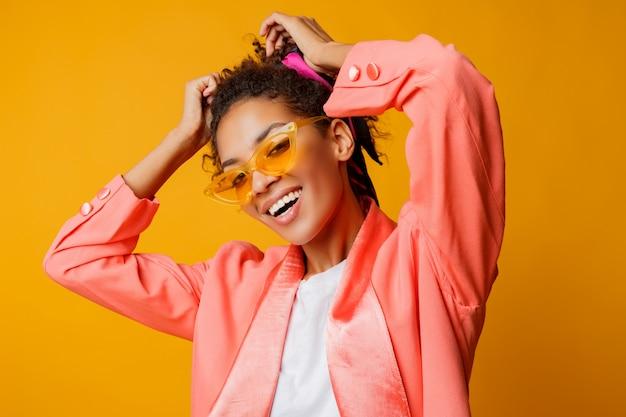 Mulher africana debonair com sorriso perfeito, cabelos encaracolados e maquiagem natural posando no casaco da moda rosa sobre fundo amarelo no estúdio.