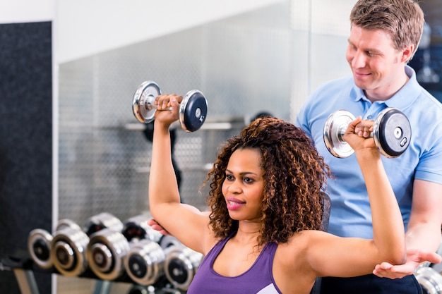 Mulher africana e treinador no exercício no ginásio