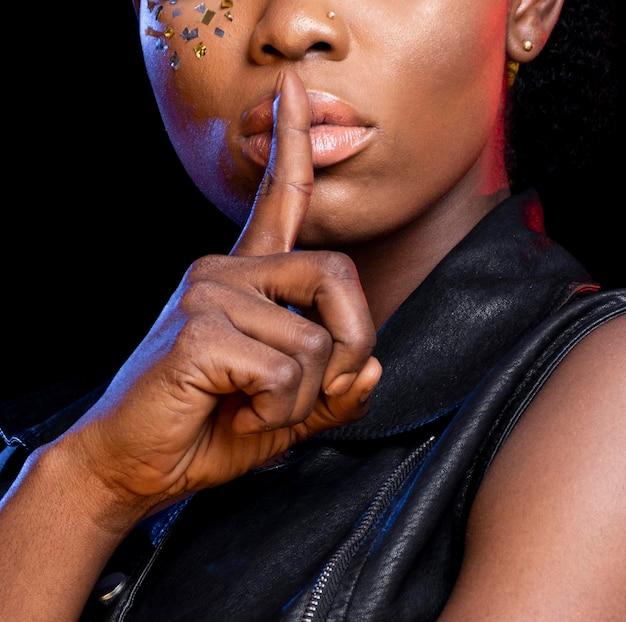 Mulher africana elegante fazendo close-up do sinal de silêncio