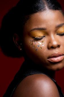 Mulher africana em colete de couro com confete brilhante nas bochechas