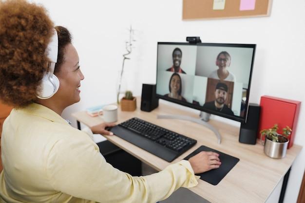 Mulher africana em videochamada com colegas usando o aplicativo de computador - foco suave à direita