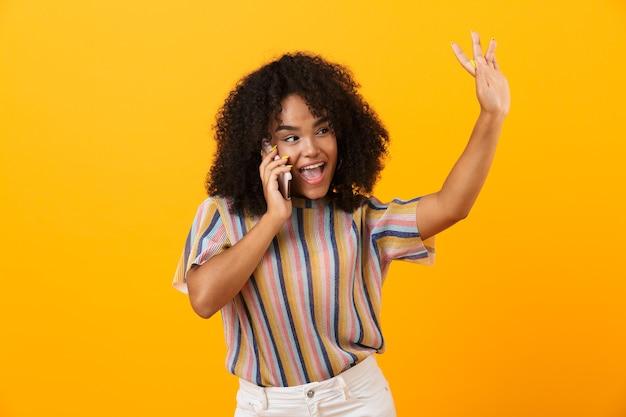 Mulher africana emocional feliz posando isolado sobre o espaço amarelo, falando por telefone celular.
