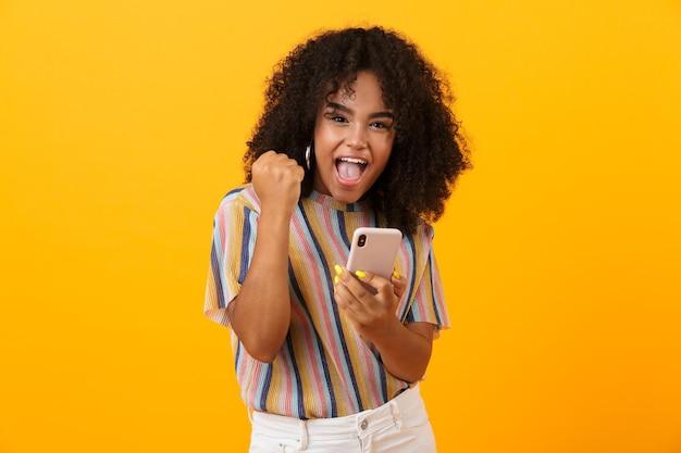 Mulher africana emocional posar isolado sobre o espaço amarelo, usando o telefone celular fazer gesto de vencedor.