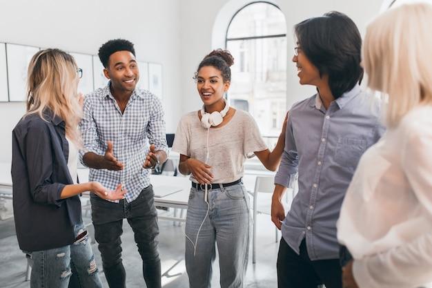 Mulher africana engraçada em jeans vintage posando entre amigos negros e asiáticos na universidade internacional. especialistas freelance reunidos com colegas estrangeiros.