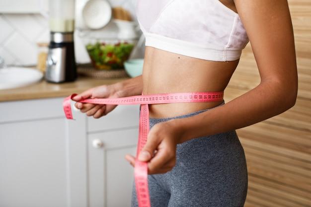 Mulher africana está medindo a cintura com um centímetro