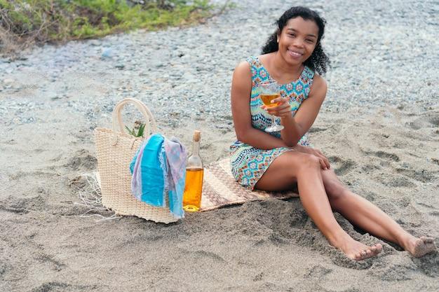 Mulher africana está sentada na praia com uma taça de vinho nas férias de verão
