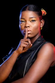 Mulher africana fazendo o sinal de silêncio