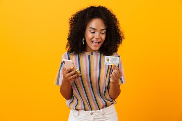 Mulher africana feliz animada posando isolado sobre o espaço amarelo, usando o telefone móvel, segurando o cartão de crédito.