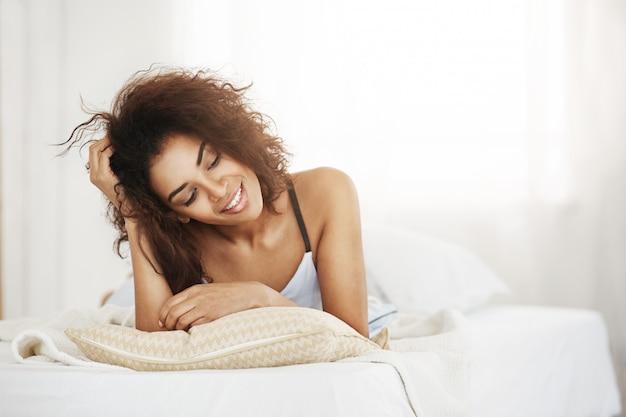 Mulher africana feliz bonita que encontra-se no travesseiro em casa que sorri sonhando.