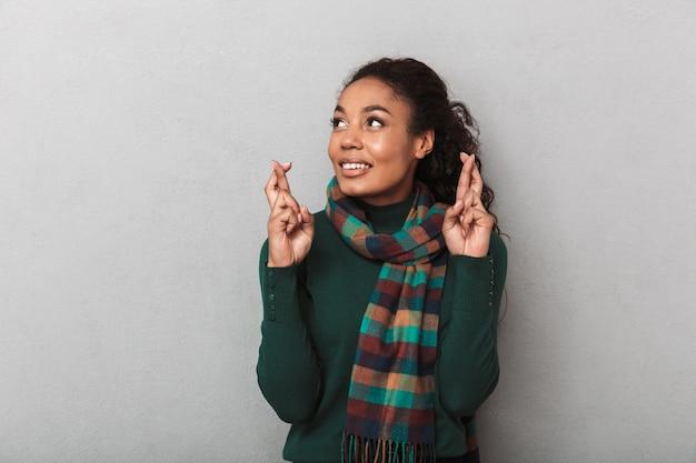 Mulher africana feliz com suéter de pé, dedos cruzados para dar sorte