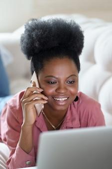 Mulher africana feliz deitada no sofá em casa, trabalhando no laptop, falando no celular inteligente