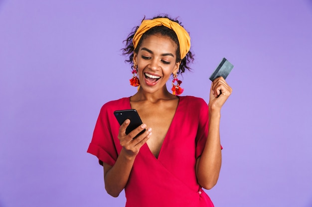 Mulher africana feliz em um vestido usando smartphone enquanto segura o cartão de crédito na parede roxa