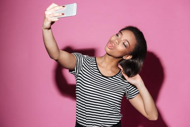 Mulher africana feliz sorridente tomando selfie