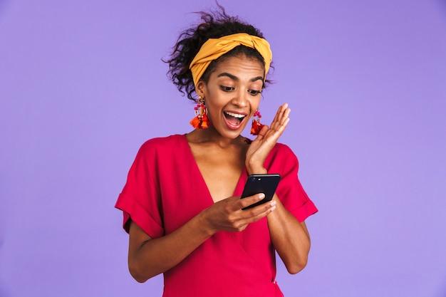 Mulher africana feliz surpresa num vestido usando smartphone e se alegra com a parede roxa