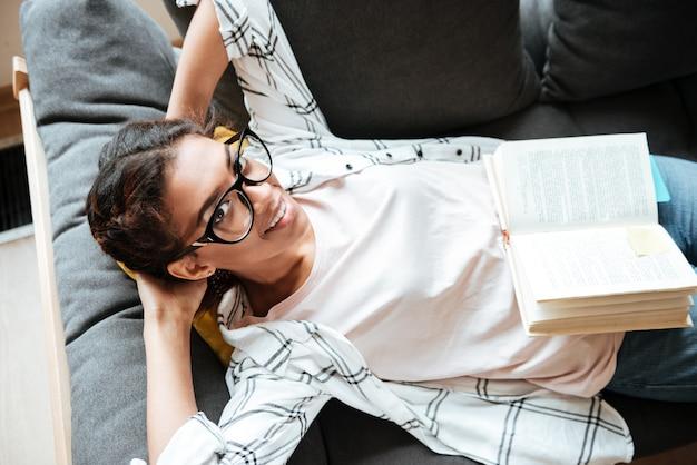 Mulher africana feliz usando óculos lendo livro.