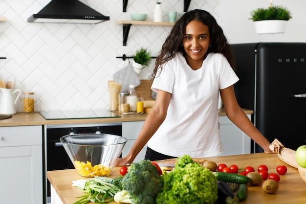 Mulher africana fica diante de uma mesa de cozinha com frutas e legumes diferentes
