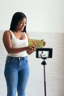 Mulher africana gravando um vídeo vlog com sua câmera de vídeo em casa