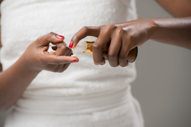 Mulher africana irreconhecível aplicando creme