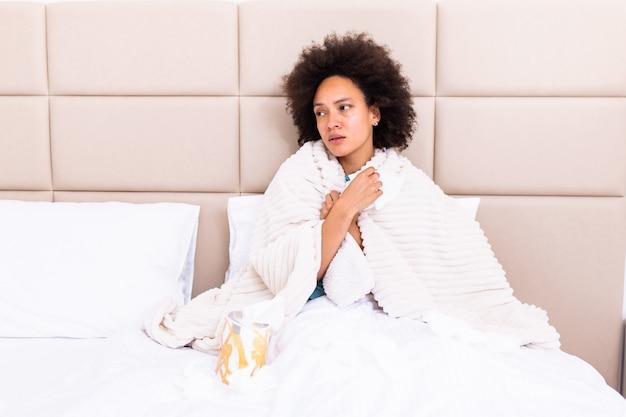 Mulher africana jovem doente, sentindo frio coberto com cobertor, sente-se na cama