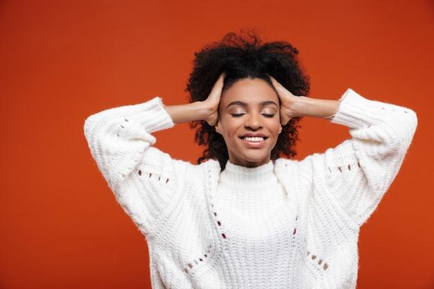 Mulher africana jovem e bonita alegre vestindo um suéter em pé sobre uma parede vermelha, olhos fechados