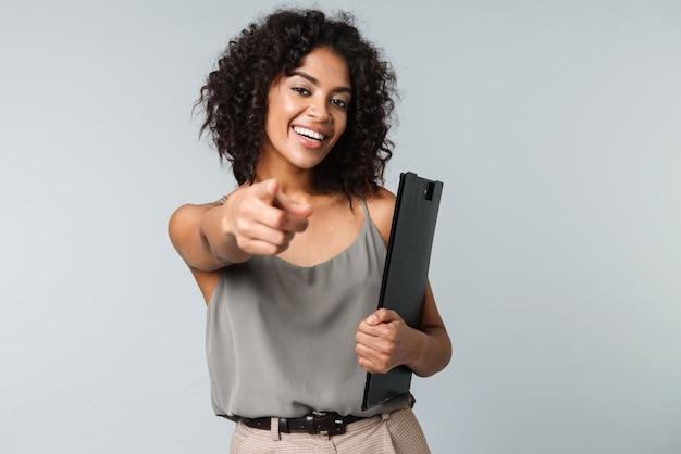 Mulher africana jovem e feliz, vestida de maneira casual, isolada, segurando um bloco de notas, apontando o dedo