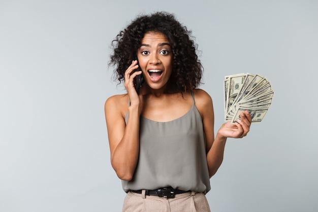 Mulher africana jovem feliz isolada, segurando um monte de notas de dinheiro, usando telefone celular
