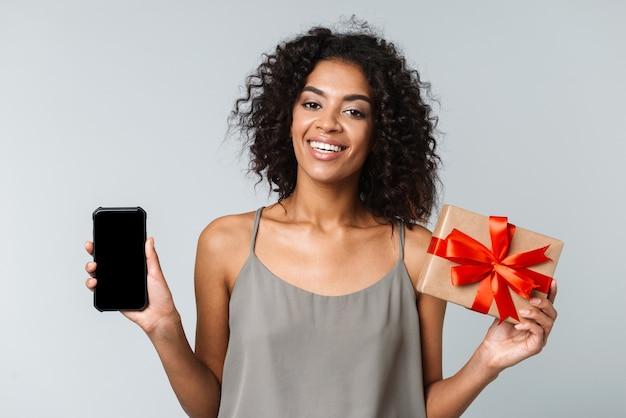 Mulher africana jovem feliz vestida casualmente de pé isolada, segurando um celular com tela em branco, mostrando uma caixa de presente