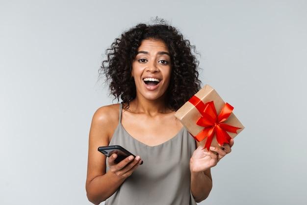 Mulher africana jovem feliz vestida de forma casual, isolada, usando telefone celular, mostrando a caixa de presente