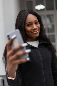 Mulher africana jovem muito feliz com um sorriso encantador em roupas da moda faz selfie no telefone celular moderno. modelo positivo de moda garota negra atraente se fotografa em smartphone na cidade.