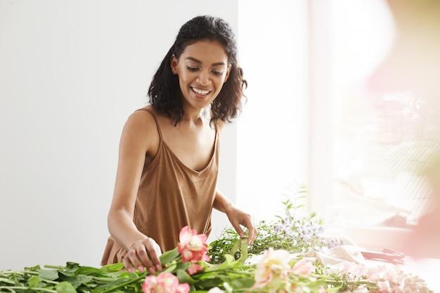 Mulher africana macia feliz que sorri fazendo o ramalhete das flores no local de trabalho sobre a parede branca.