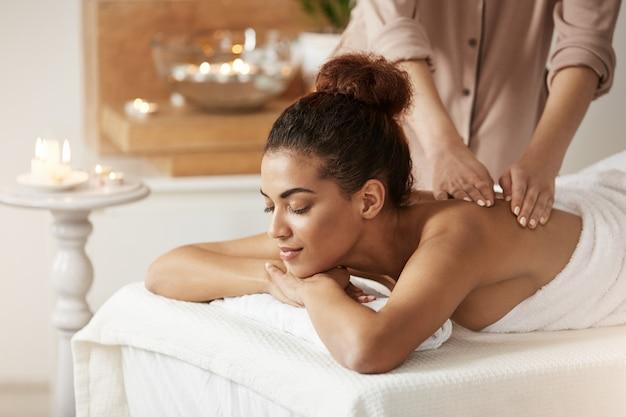 Mulher africana macia que sorri apreciando a massagem com os olhos fechados no spa resort.