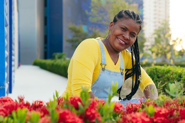 Mulher africana madura posando perto de flores vermelhas ao ar livre