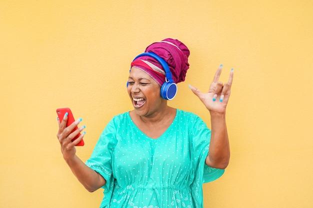 Mulher africana madura usando aplicativo de smartphone para criar playlist com música rock - mulher sênior se divertindo com tecnologia de telefone celular - conceito de estilo de vida de idoso alegre e tecnológico