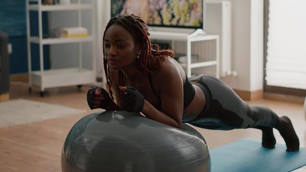 Mulher africana magra alongando o músculo abdominal enquanto está sentada na bola suíça de ioga, fazendo exercícios matinais na sala