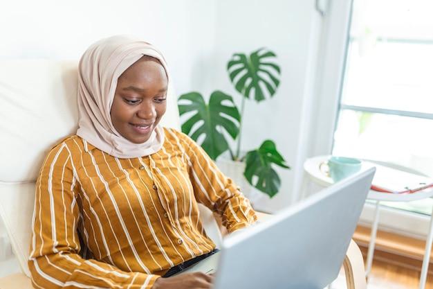 Mulher africana muito muçulmana feliz usando laptop sentado no sofá aconchegante. bela jovem muçulmana está usando um laptop e sorrindo enquanto está sentada no sofá em casa