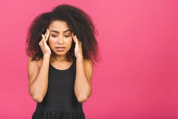 Mulher africana nervosa respirando acalmando, aliviando a dor de cabeça ou gerenciando o estresse, garota negra se sentindo estressada massageando as têmporas exalando na rosa.