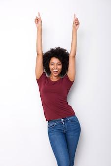 Mulher africana nova feliz que aponta os dedos acima no excitamento no fundo branco