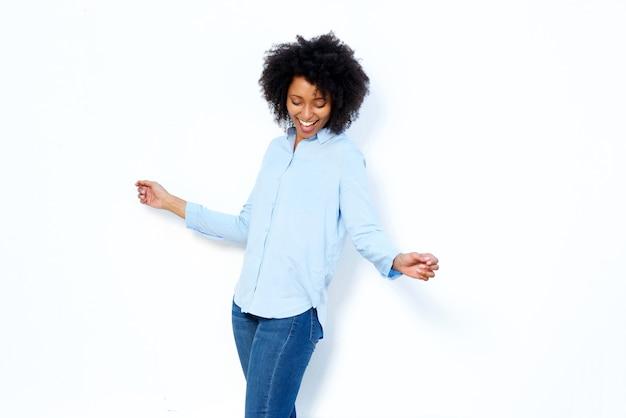 Mulher africana nova feliz que dança e que aprecia de encontro ao fundo branco