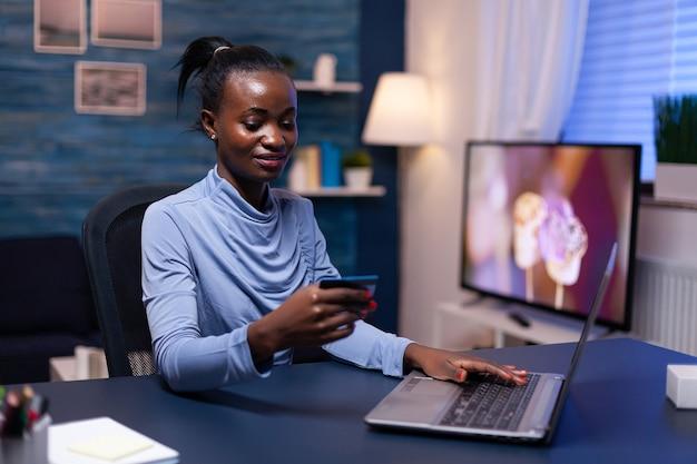 Mulher africana olhando para dados de digitação de código de segurança cw no webstite para a loja da web. funcionário que faz a transação do paymant em casa no notebook digital.