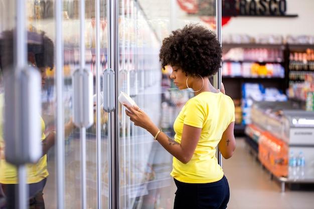 Mulher africana pegando o produto na geladeira do supermercado.