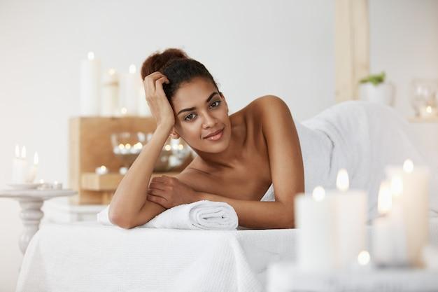 Mulher africana relaxante no salão spa sorrindo.