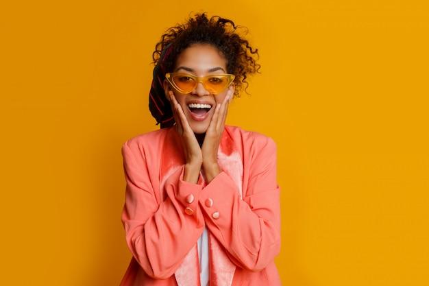 Mulher africana rindo sobre fundo amarelo. emoções verdadeiras, cara de surpresa. olhar na moda.
