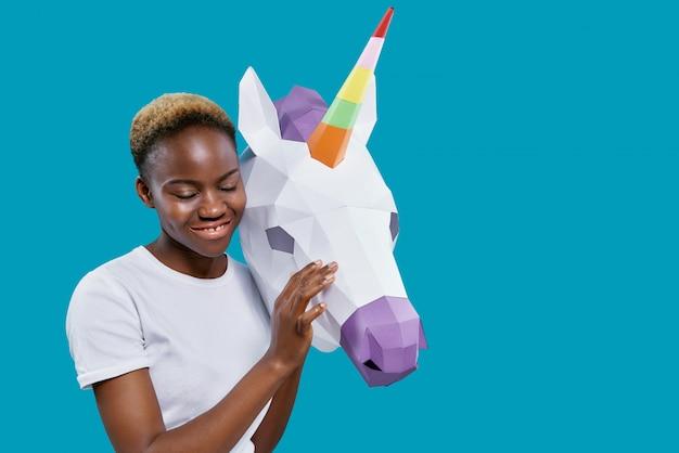 Mulher africana segurando 3d cabeça de unicórnio de papel.
