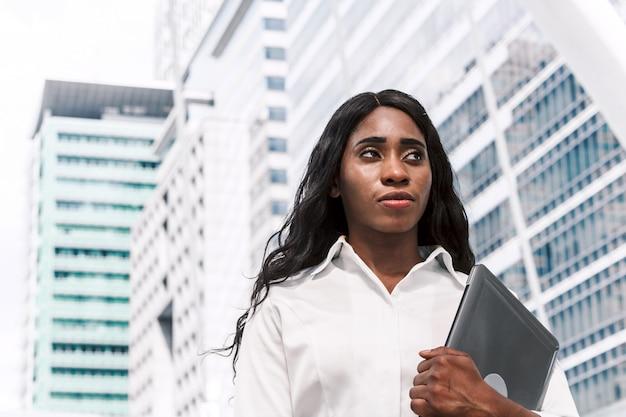 Mulher africana, segurando, laptop, ligado, edifício escritório, fundo