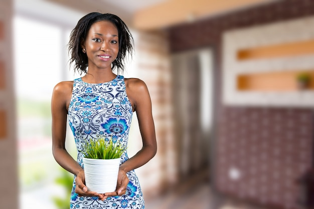 Mulher africana, segurando, planta vaso