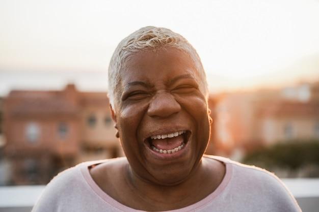 Mulher africana sênior feliz sorrindo para a câmera ao ar livre na cidade - foco no rosto