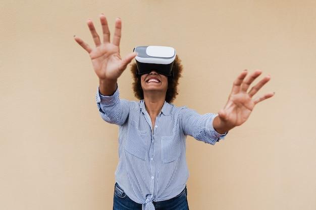 Mulher africana sênior feliz usando fone de ouvido de realidade virtual - foco nos óculos de vr
