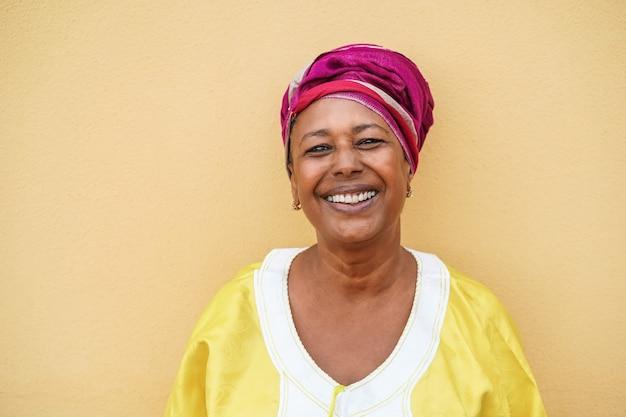 Mulher africana sênior feliz usando um vestido tradicional, olhando para a câmera - foco no rosto